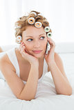 Woman in hair curlers using cellphone while lying in bed