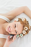 Relaxed woman in hair curlers using cellphone in bed