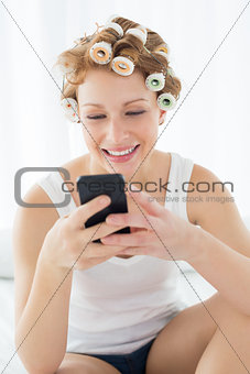 Woman in hair curlers text messaging on bed