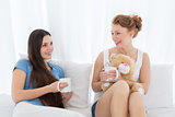 Cheerful female friends with coffee cups in bed