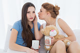 Female friends with coffee cups gossiping in bed