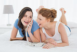 Happy woman with friend using phone in bed