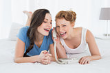 Cheerful woman with friend using phone in bed