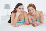 Happy female friends in teal tank tops lying in bed