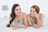 Female friends in teal tank tops lying in bed