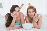 Female friends with remote control and popcorn in bed