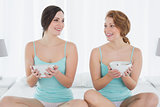 Smiling female friends with salad bowls sitting on bed