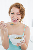 Cheerful young female with a bowl of cereal on bed