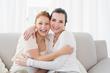 Cheerful female friends embracing in living room