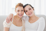 Happy female friends with arm around in the living room