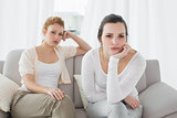 Unhappy friends not talking after argument on the couch