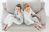 Unhappy young female friends not talking after argument on the couch