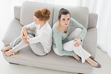 Unhappy female friends not talking after argument on the couch