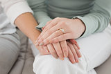 Close-up mid section of female friends touching hands