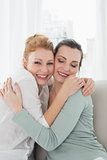 Cheerful young female friends embracing in living room