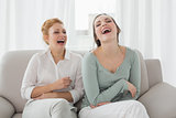 Female friends laughing while sitting on sofa in the living room