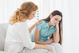 Young woman consoling female friend at home