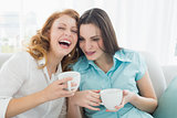 Friends with coffee cups enjoying a conversation at home