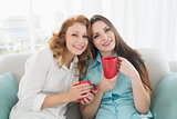Female friends with coffee cups in the living room