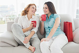 Female friends with coffee cups conversing at home