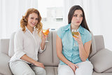 Female friends with wine glasses sitting on sofa