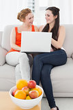 Female friends using laptop together at home