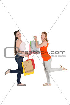 Happy young female friends with shopping bags