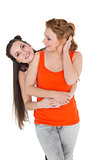 Cheerful young female embracing her friend from behind