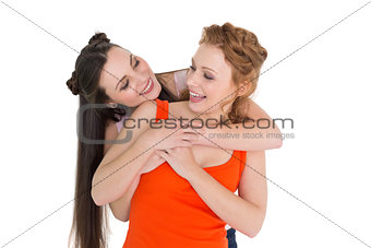 Young female embracing her cheerful friend from behind