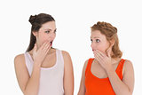 Two young shocked female friends with hand over mouth