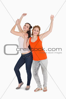 Portrait of two cheerful young female friends dancing