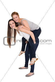 Full length portrait of a young female piggybacking friend