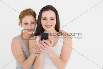 Casual young female friends looking at mobile phone