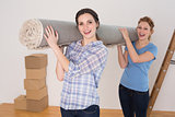 Cheerful friends carrying rolled rug after moving in a house