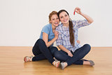 Female friends with house keys sitting on the floor