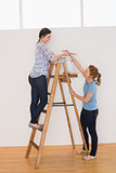 Two female friends with a ladder in a new house
