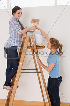 Friends with paintbrush and can on ladder in a new house