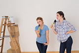Friends singing into paintbrushes by ladder in a new house