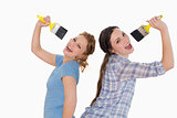 Cheerful female friends singing into paintbrushes