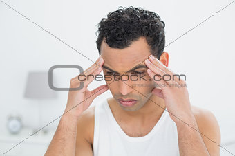 Close-up of a man suffering from headache in bed
