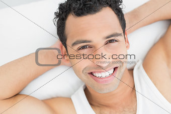 Close-up portrait of a cheerful man resting in bed