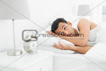 Sleepy man looking at the alarm clock in bed