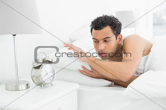 Sleepy man looking at the alarm clock in bed