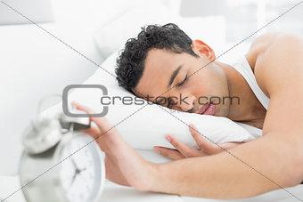 Man in bed extending hand to alarm clock