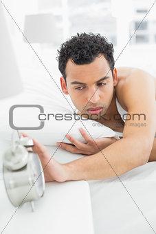 Sleepy man extending hand to alarm clock