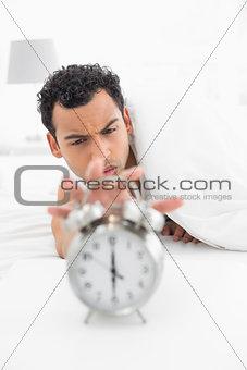 Sleepy man in bed extending hand to alarm clock