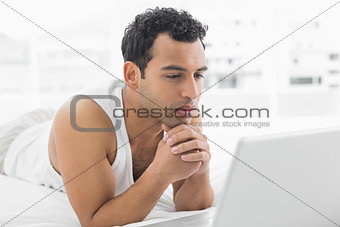 Casual man using laptop in bed