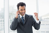 Elegant young businessman using cellphone in office