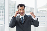 Cheerful elegant young businessman using cellphone in office