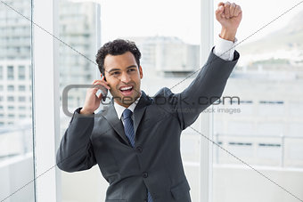 Cheerful elegant businessman using cellphone in office